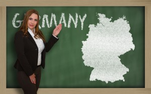 Successful, beautiful and confident young woman showing map of germany on blackboard for presentation, marketing research and tourist advertising